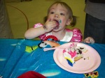 She was using her fork but gave up when the cake kept falling off.